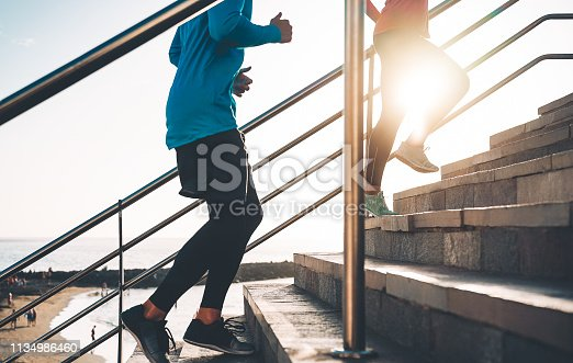 View of runners legs training outdoor - Young couple doing a workout session on stairs next the beach at sunset - Healthy people, jogging and sport lifestyle concept