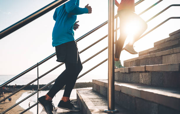 view of runners legs training outdoor - young couple doing a workout session on stairs next the beach at sunset - healthy people, jogging and sport lifestyle concept - men shoes stock pictures, royalty-free photos & images