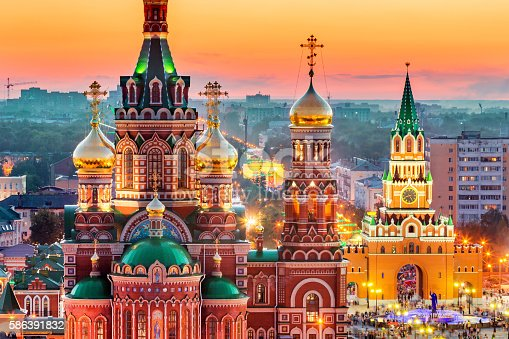 Nice view of the town at sunset. Orthodox church surrounded by beautiful red brick buildings on the city's embankment. Volga region of Russia, the city of Yoshkar-Ola