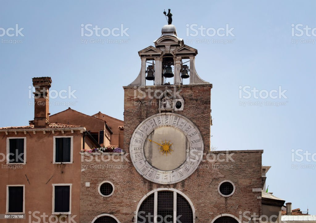 View of San Giacomo di Rialto Church with blue sky background in Venice / Italy. Catholic gothic building dating to circa 1071 CE, with a large, iconic 15th-century clock on its facade. stock photo