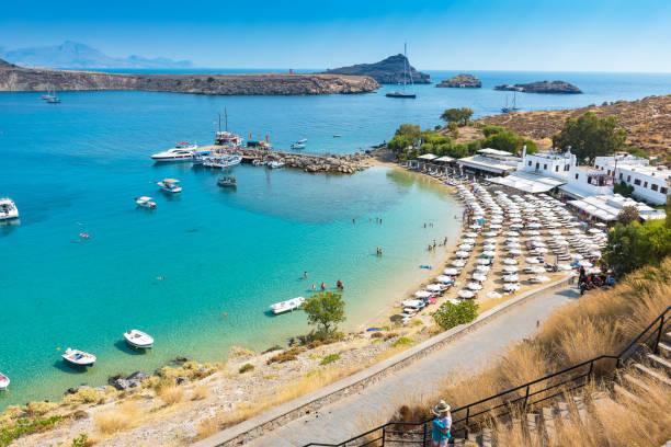weergave van het zandstrand in de baai van lindos (rhodos, griekenland) - rondvaartboot stockfoto's en -beelden
