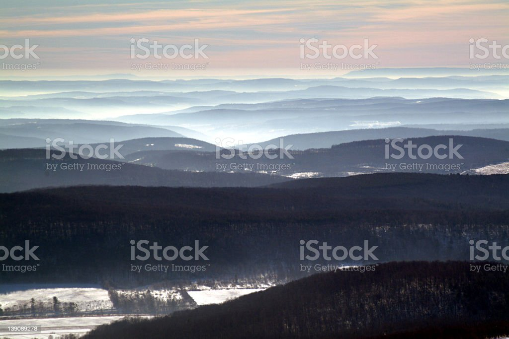 View of several dark hills in the winter under a dim sky stock photo