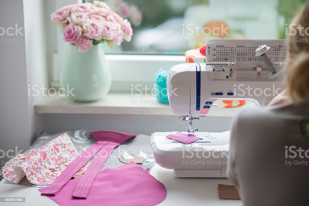 view of sewing room with sewing machine, fabric, flowers stock photo