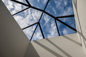 Looking up at the ceiling of a home through a large and elegant skylight. Interesting lines and shadows play together to create a dynamic composition that capture the stye of modern architecture and interior design.