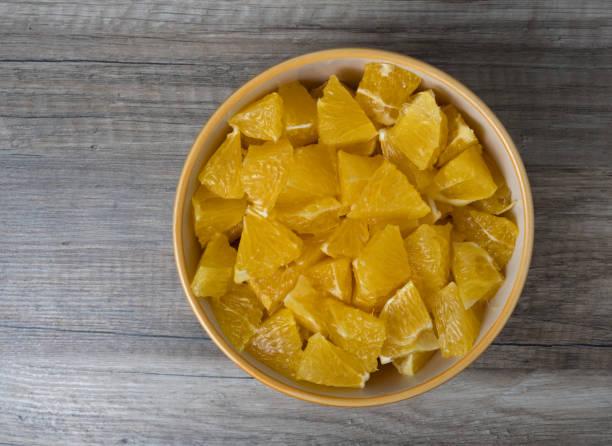 Blick auf in Scheiben geschnittene Orangen in einer Schüssel, auf Holzhintergrund. – Foto