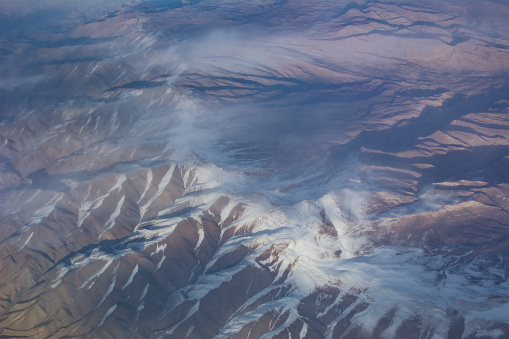 istock View of snowy high mountain from airplane 1030296142