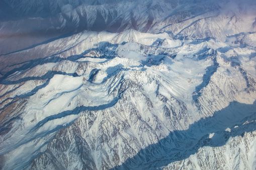 istock View of snowy high mountain from airplane 1030296148