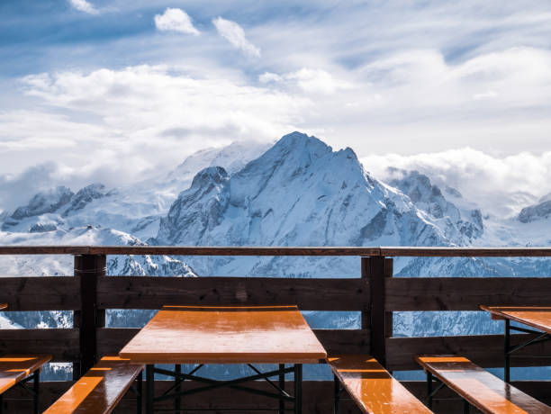 View of snowy mountains from restaurant in the alps. Lunch break from skiing in the sun. Empty tables and seats in foreground. stock photo