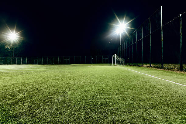 View of soccer field illuminated at night View of soccer field illuminated at night turf stock pictures, royalty-free photos & images
