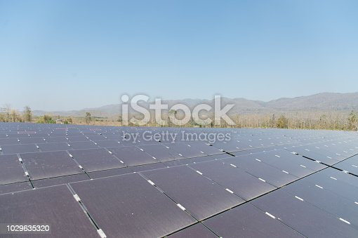 istock View of solar farm in sunlight with blue sky, dirty solar cell  array, green energy concept. 1029635320