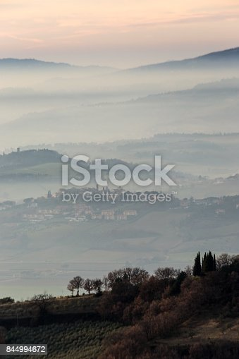 istock A view of some trees in the foreground with layers of hills and towns through the mist in the background 844994672