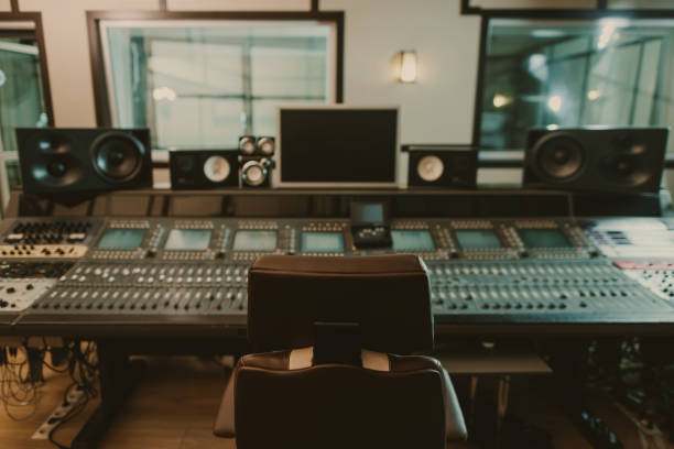 view of sound producing equipment at recording studio with armchair on foreground view of sound producing equipment at recording studio with armchair on foreground recording studio stock pictures, royalty-free photos & images
