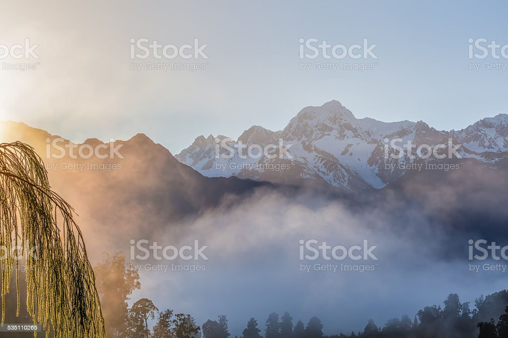 View of Southern Alps from lake Matheson, early morning mist stock photo
