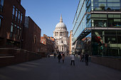 London, England - March 10, 2015: View of St Paul's Cathedral, on the right is the offices of the Salvation Army and Café. People can be seen, Blue sky and Cathedral