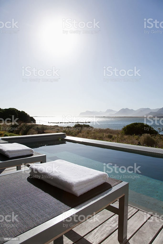 View of sun shining on lake from patio with swimming pool royalty-free stock photo