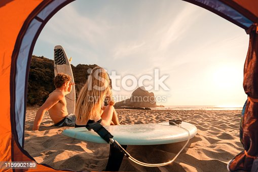 istock View of surfers from tent enjoying sunset at beach. 1159902189