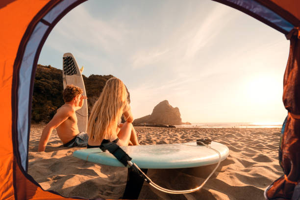 View of surfers from tent enjoying sunset at beach. stock photo