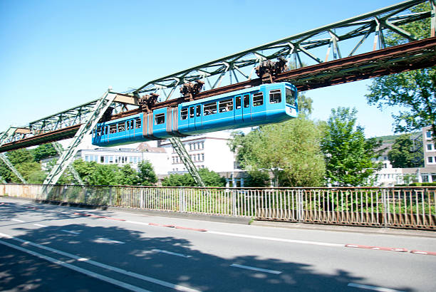 View of Suspension Railway in Schwebebahn Wuppertal, Germamy Famous Schwebebahn of Wuppertal, North-Rhine-Westphalia, Germany. This mode of transport is basicaly used like a tram or metro but faster because of no traffic lights. There is a saying: Once in your life, through Wuppertal you drive (German: einmal im Leben durch Wuppertal Schweben). The track is build over the river Wupper north rhine westphalia stock pictures, royalty-free photos & images