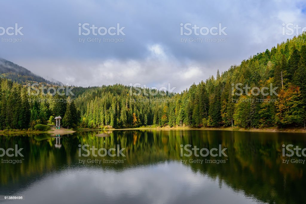 View of Synevir high-altitude lake by autumn day. The leaf fall forest is reflected in water of lake. stock photo