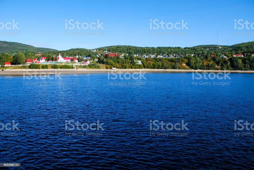 view of tadoussac bay in canada from a ferry boat on blue sky and water backgrounds stock photo