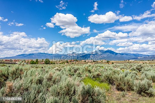View of Taos Sangre de Cristo mountains view from Ranchos de Taos valley and green landscape in summer with clouds