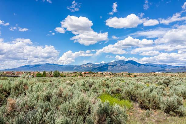 Vista da vista das montanhas de Taos sangre de Cristo do vale de ranchos de Taos e da paisagem verde no verão com nuvens - foto de acervo