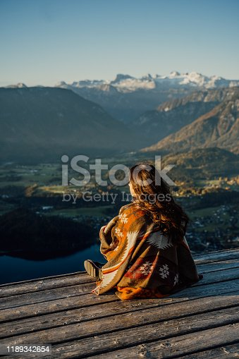 629376126istockphoto View of teenage girl with poncho sitting on view point 1189342654