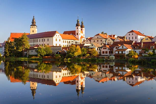 view of telc across pond with reflections, southern moravia, czech republic. - чехия стоковые фото и изображения