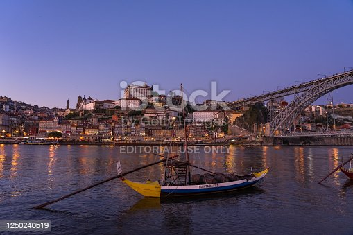 Porto, Portugal - December 01, 2019: View of the A Ribeira and the city of Porto since Aldeina Nova at night with the typical ravelo boats.