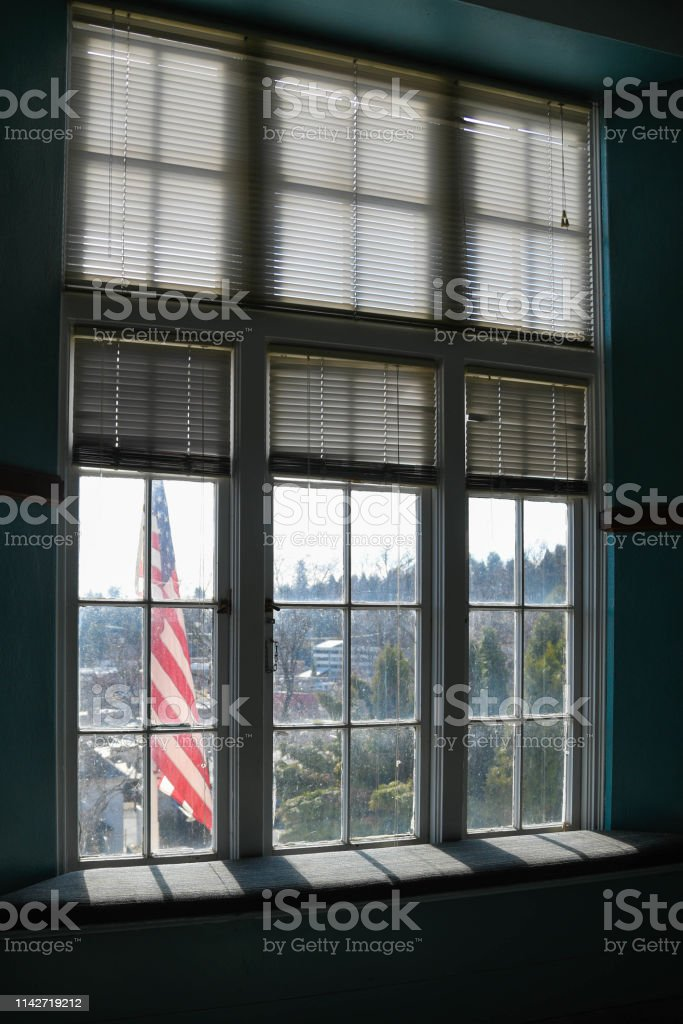 The American flag is seen out the window seat of an elementary school.