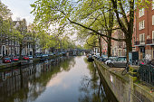 AMSTERDAM, NETHERLANDS - April 2, 2019: view of the Amsterdam channel with the houses on the water. Early morning day