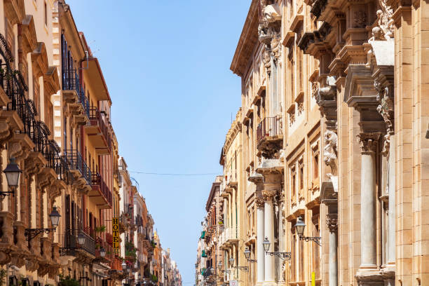View of the apartments and businesses under a clear blue sky on a beautifully restored Trapini Sicily Street