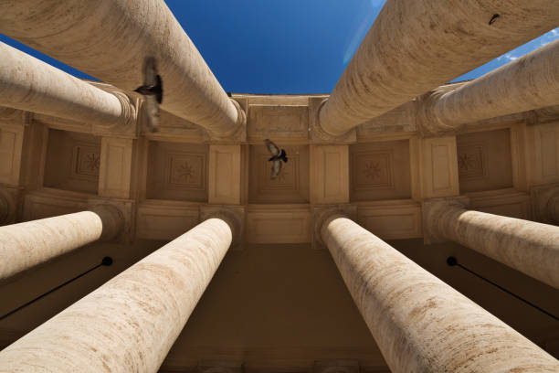 view of the bernini's colonnade from the bottom to the top with pigeons flying trough - low angle view foto e immagini stock