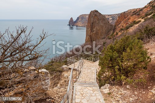 istock View of the Black Sea coast in Crimea, Cape Fiolent in Sevastopol. Panoramic seascape, calm azure sea, clouds and bright sky. 1311296700