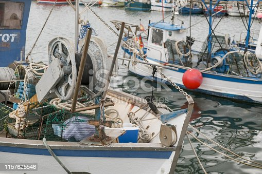 View of the fishing boats in the port. Mooring of the small fishing vessel at the dock. Fishing gear and equipment on the boat. Preparing to sail.