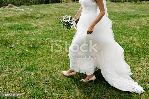 view of the bottom bride walking back on a trail in an green park. Young girl in an elegant dress is standing on the field near the forest and holding bouquet flowers at nature. Outdoors.