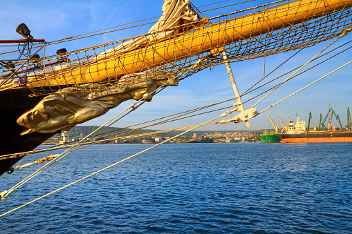 View of the bow and the figurehead of a sailing ship close-up against the background of the port of Varna, on the Black Sea coast of Bulgaria
