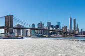 View of the Brooklyn Bridge, the coastline and the East River with snow and ice during a cold winter at Manhattan, New York, USA.