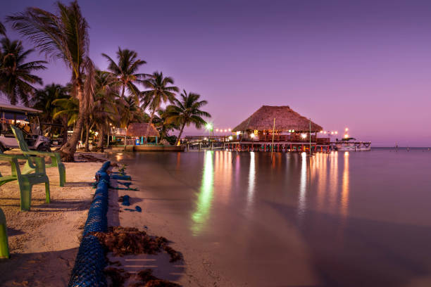A view of the bungalow overwater beautifully lit up at dusk in Belize.