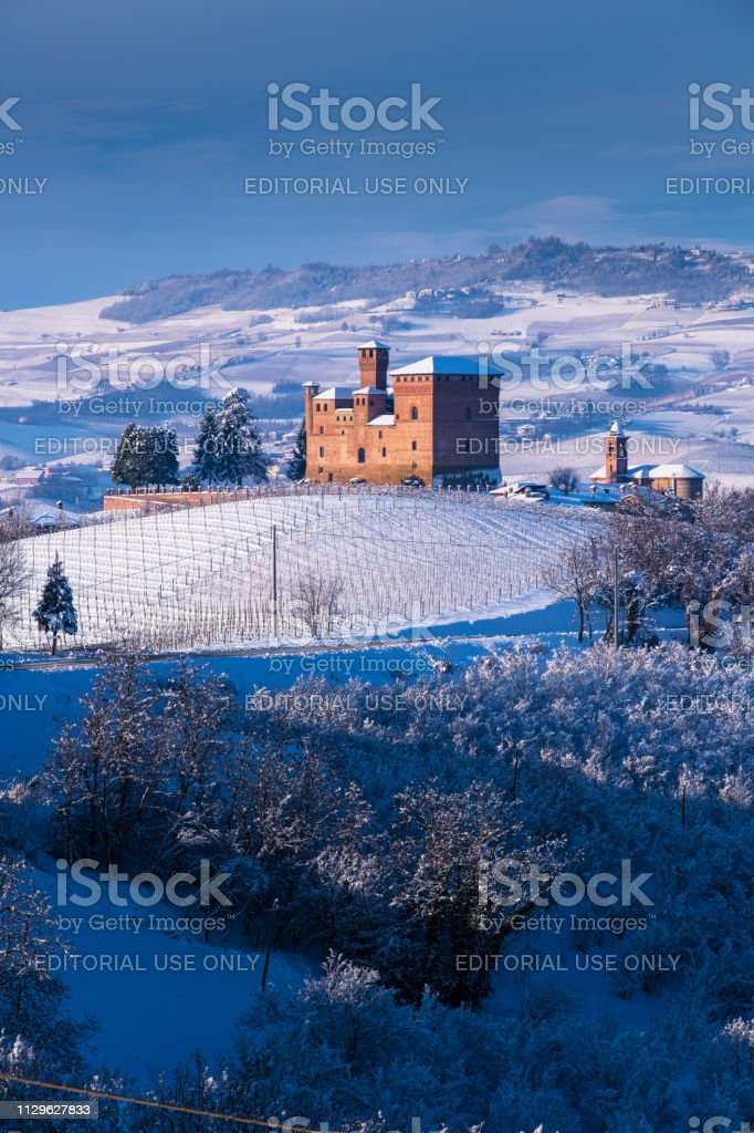 View of the Castle of Grinzane Cavour Unesco symbol surrounded by hills and snowy vineyards - foto stock
