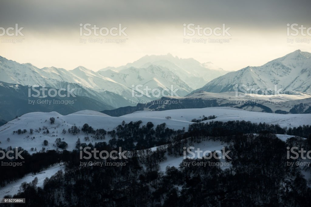 view of the Caucasian ridge with clouds hanging on tops of mountains stock photo