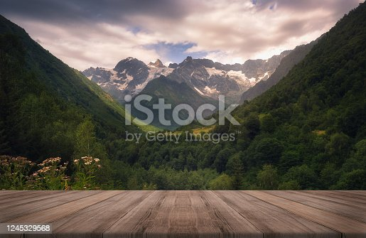 View of the Caucasus mountain range in Racha, Georgia. Beautiful background with empty wooden table. Natural template landscape