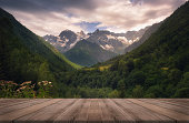 istock View of the Caucasus mountain range in Racha, Georgia. Summer beautiful background with empty wooden table. Natural template landscape 1245329568