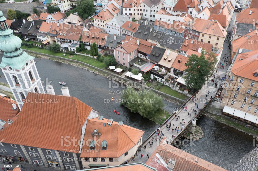 View of the charming medieval town, Cesky Krumlov, from the Castle Tower. People crossing a bridge over the Vltava River to the Church of St Jost (Kostel sv Josta). stock photo