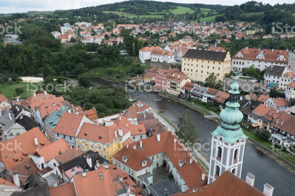 View of the charming medieval town, Cesky Krumlov, from the castle tower. Looking over the town from high up, Church of St Jost overlooking the Vltava River flowing through the town green hills beyond stock photo