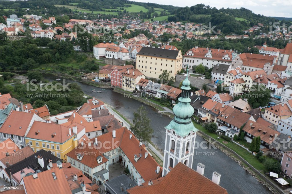 View of the charming medieval town, Cesky Krumlov, from the castle tower. Looking over the town from high up, Church of St Jost overlooking the Vltava River flowing through the town. stock photo