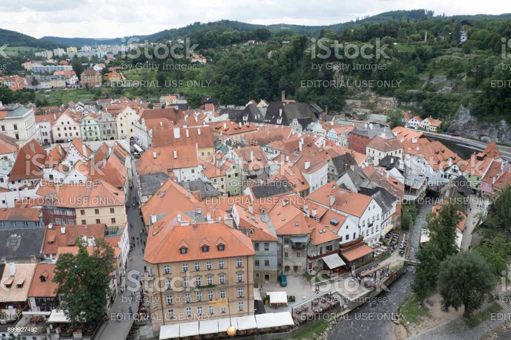 View of the charming medieval town, Cesky Krumlov, from the castle tower. People eating outside next to the Vltava River and walking down the street. stock photo