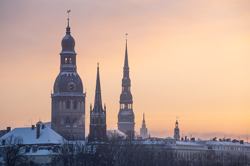 Sunrise on early winter morning, three church towers of Old Riga can be seen in the background