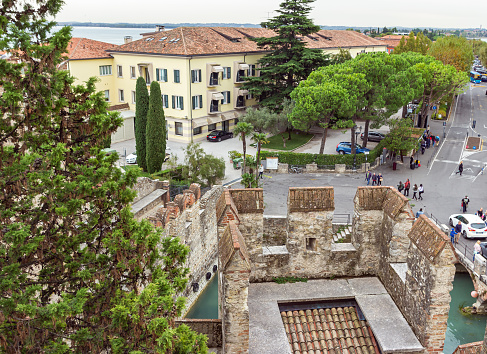 View of the city located behind the walls of the Castello Scaligero fortress in the Sirmione town in Lombardy, northern Italy