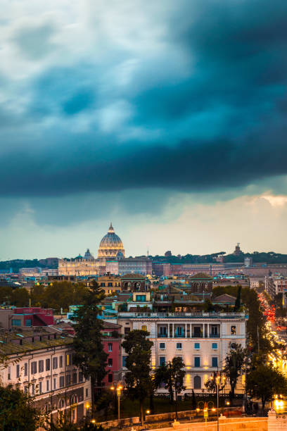 View of the city of Rome at sunset with a storm on the dome of St. Peter's Basilica in Vatican View of the city of Rome at sunset with a storm on the dome of St. Peter's Basilica in Vatican lazio stock pictures, royalty-free photos & images